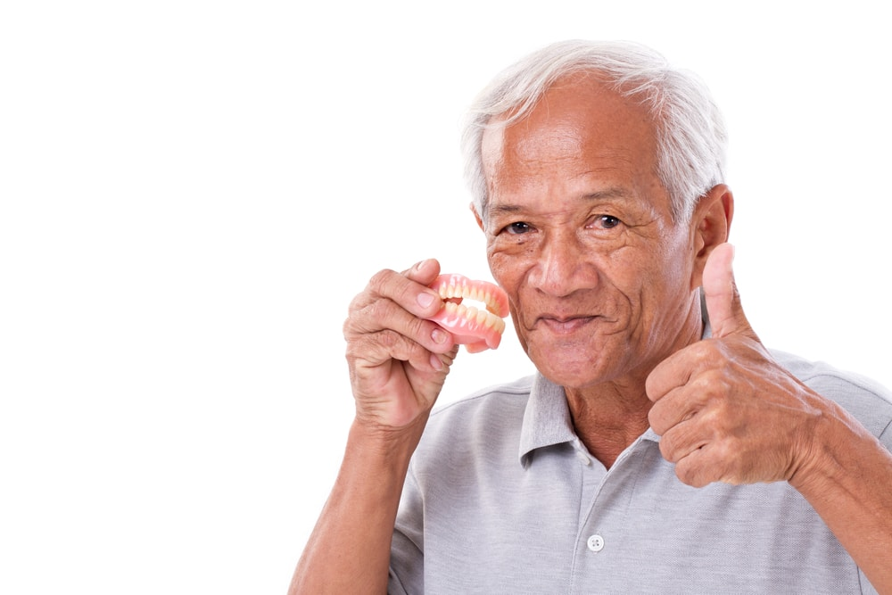 Elderly man holding dentures in hand